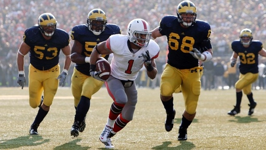 FILE - In this Nov. 21, 2009 file photo, Ohio State running back Dan Herron (1) scores a touchdown on a 12-yard reception as the Michigan defense chases during the third quarter of an NCAA college football game in Ann Arbor, Mich.  So you're the Big Ten or Pac-10 and you're trying to decide how to split your new, 12-team league into two divisions while keeping traditional rivalries intact and avoiding competitive imbalance and geographic oddities. The SEC, ACC and Big 12 have been through this before _ and their experiences may offer a few lessons. (AP Photo/Paul Sancya, File)