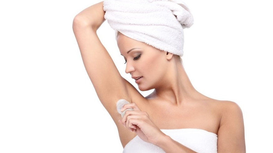 Young beautiful lady with a towel on her head applying deodorant