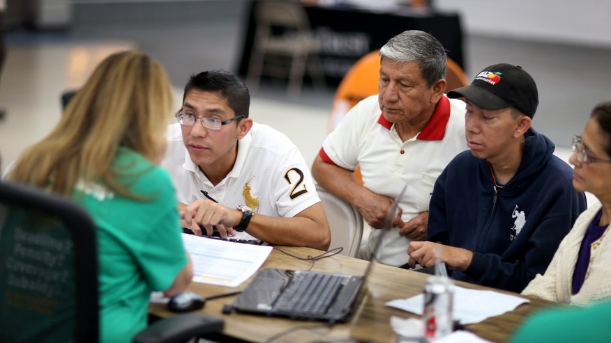 MIAMI, FL - MARCH 20:   Paul Paucar (L-R), Homero Paucar, Giovanny Paucar and Ivonne Cucalon sit with, Jessica Adames, an insurance agent from Sunshine Life and Health Advisors as they try to purchase health insurance under the Affordable Care Act at a store setup in the Mall of Americas on March 20, 2014 in Miami, Florida. The owner of Sunshine Life and Health Advisors, Odalys Arevalo, said she has seen a surge in people, some waiting  up to 3 hours or more in line, trying to sign up for the Affordable Care Act before the open enrollment period for individual insurance ends on March 31.  (Photo by Joe Raedle/Getty Images)