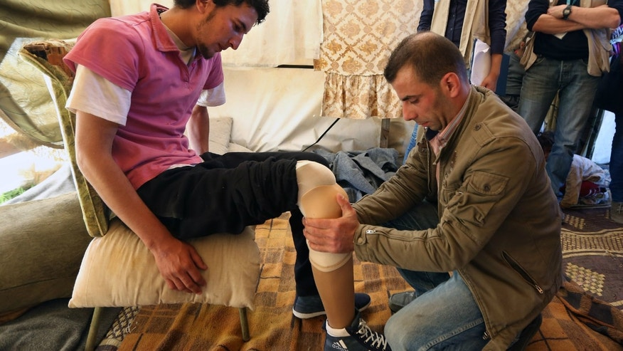 Mustafa Ahmad, left, a 19-year-old who lost his leg in his hometown of Deir Hafer in Aleppo province in November 2011 when government warplanes bombed his neighborhood, is fitted with a prosthetic leg by a Lebanese prosthetic limb maker, right, at the Syrian refugee camp in Jib Janine, in the Bekaa valley, Lebanon.