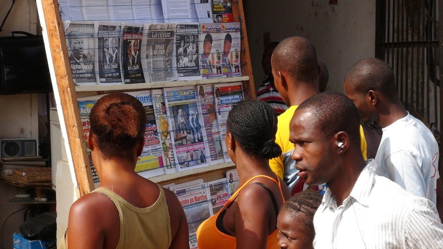 People read news headlines at a newsstand in Conakry, Guinea, March 28, 2014. (REUTERS/Saliou Samb)