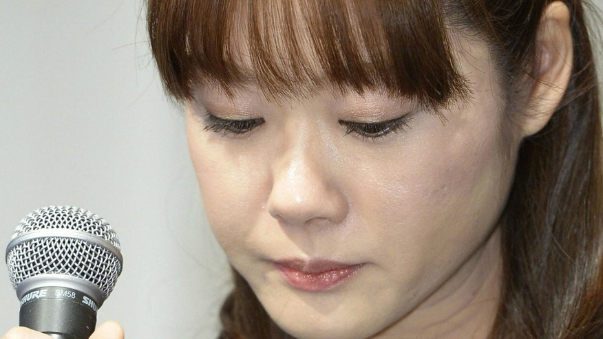 Haruko Obokata, a researcher at semi-governmental research institute RIKEN, lowers her eyes during a news conference in Osaka, western Japan. Last week, RIKEN accused Obokata, the lead writer of stem cell papers hailed as a game-changer in the field of medical biology, of misconduct involving fabrication, but the scientist called the findings unacceptable.