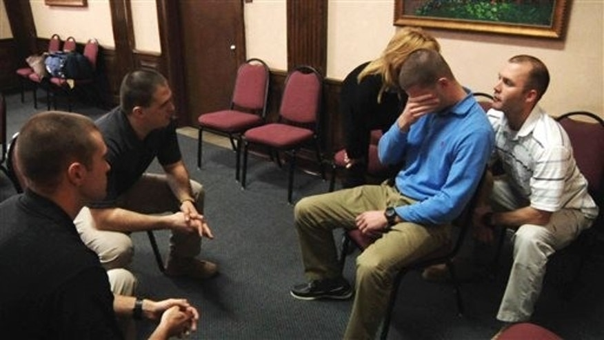 In this image taken from video on Jan. 15, 2014, from left, Lower Merion police officers Edward Sarama and Robert McGuire try to talk to Lower Merion officer Matt Dougherty, seated right in blue, who is pretending to be mentally ill, during a training simulation at Montgomery County Emergency Service in Norristown, Pa. Talking in Dougherty's ears to simulate voices in his head are course instructor Michelle Monzo and Lower Merion Township officer Joe Smith. The training is designed to help police recognize and respond to  people suffering from serious mental illness, potentially reducing injuries to officers and the mentally ill as well as the frequency of arrests. (AP Photo/Michael Rubinkam)