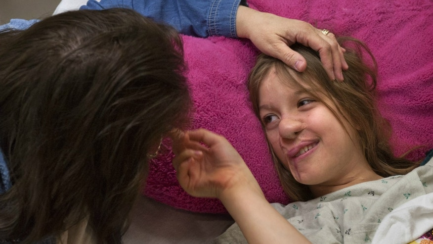 Charlotte Ponce, 11, waits with her mom Sharon Ponce at Beaumont Children's Hospital in Royal Oak, Mich., Tuesday, April 15, 2014. Charlotte is having a plastic surgeon create an ear for her after she suffered severe injuries to her face in a raccoon attack when she was an infant.