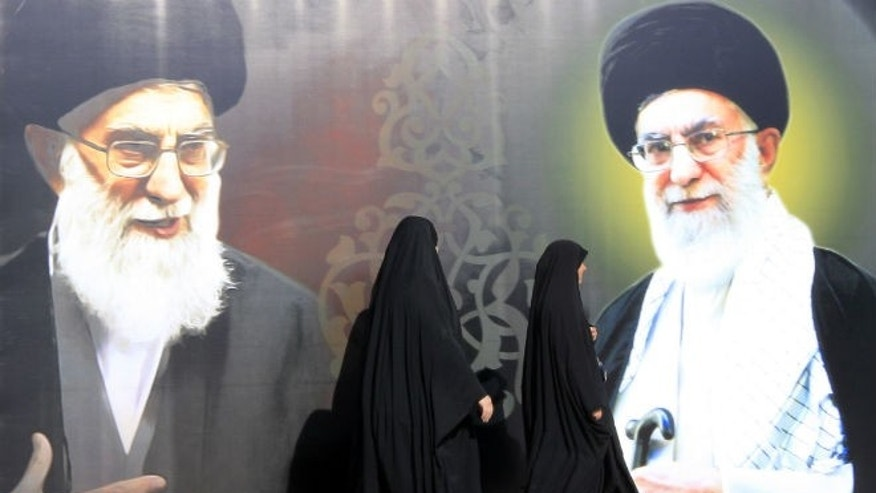 Iraqi women walk past a poster depicting images of Shi'ite Iran's Supreme Leader Ayatollah Ali Khamenei at al-Firdous Square in Baghdad February 12, 2014. (REUTERS/Ahmed Saad)