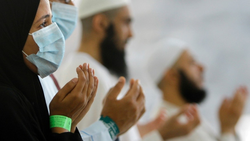 Egyptian Muslim pilgrims, some wearing masks as a precaution against the Middle East respiratory syndrome, pray during the last rite of the annual hajj, near the Muslim holy city of Mecca, Saudi Arabia. (AP Photo/Amr Nabil, File)
