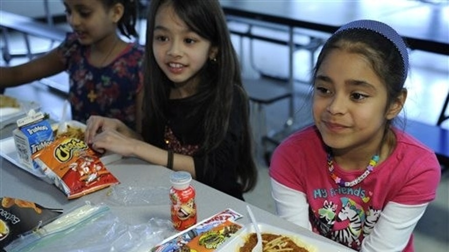 Brianna Delcid-Gomez, 7, right, sitting with Ruth Gebregiorgis, 8, left, and Amina Sharif, 7, center, eat lunch at the Patrick Henry Elementary School in Alexandria, Va., Tuesday, April 29, 2014. (AP Photo/Susan Walsh)