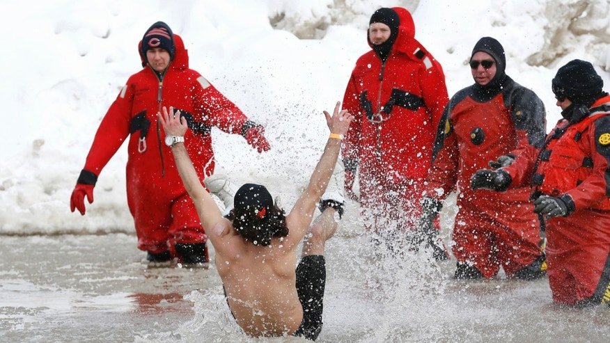 Rescue workers look on as a participant  jumps into Lake Michigan as he takes part in the Annual Polar Plunge in Chicago, March 2, 2014. After a recent surge in popularity, cold-water challenges are prompting warnings over their risk for injuries. (REUTERS/Jim Young)