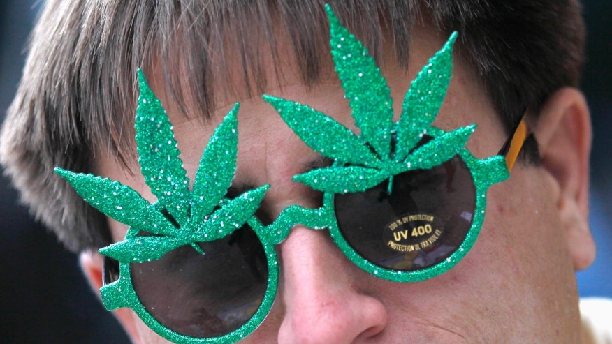 A man wears novelty sunglasses adorned with artificial marijuana leaves as he sells them across the street from a pro-marijuana rally at the University of Colorado in Boulder, Colorado April 20, 2012. (REUTERS/Rick Wilking)