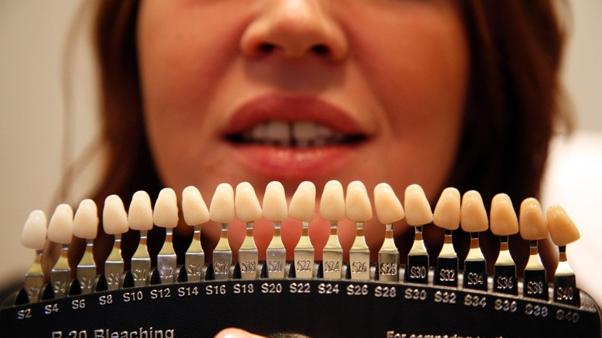 A tooth colour chart is used to evaluate the current colour before a customer undergoes a teeth whitening treatment.