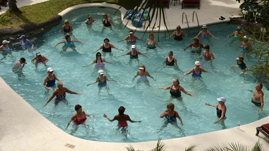 People take part in an aqua aerobics session in a swimming pool at a resort at Holetown, Barbados  March 7, 2014. (REUTERS/Philip Brown)