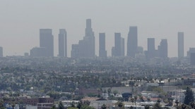 The skyline of downtown Los Angeles through a layer of smog is seen in the distance from a rooftop in Hollywood, California, May 31, 2006. (REUTERS/Fred Prouser/Files)