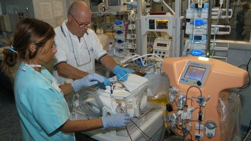 In this image made available by the San Bortolo Hospital in Vicenza a nurse Mariangela Mettifogo, left, and Dr. Claudio Ronco treat a baby hooked up to a new dialysis machine at the San Bortolo Hospital in Vicenza, Italy, in the  summer of 2013.