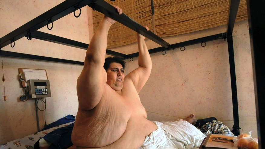 Manuel Uribe shows how he exercises from his bed during an interview on June 9, 2008 in Monterrey, Mexico.