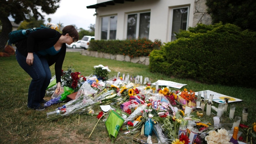 A student lays flowers at a makeshift memorial in front of the Alpha Phi sorority house where two women were killed in the Isla Vista neighborhood of Santa Barbara, California May 26, 2014. (REUTERS/Lucy Nicholson)