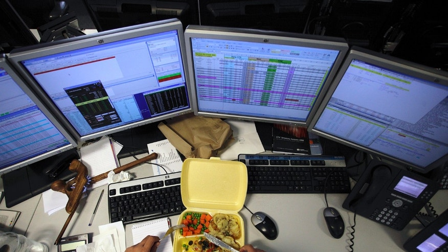 A dealer eats his lunch as he monitors his screens on the trading floor of IG Index in London May 6, 2010. (REUTERS/Kevin Coombs)