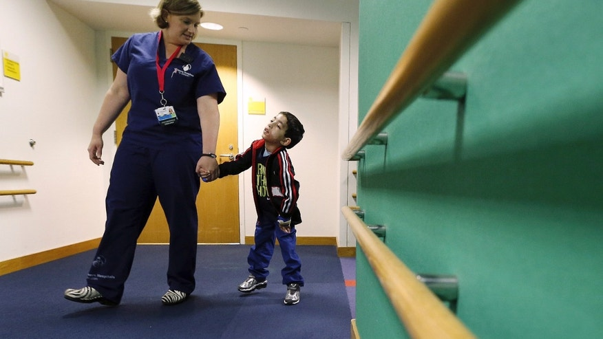 Therapist Katherine Hartigan walks with Ihor Lakatosh at Shriners Hospital for Children in Boston. (AP Photo/Michael Dwyer)