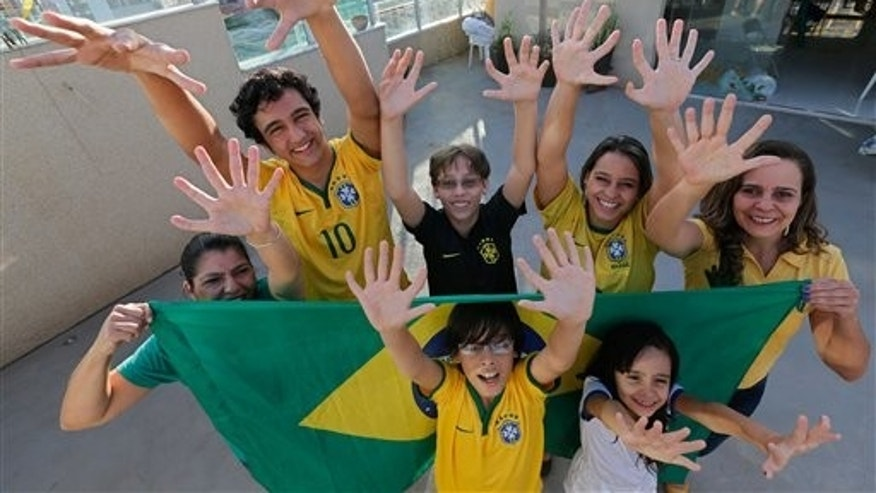 Members of the Silva family, back row, from left, Silvia Santos, Joao de Assis, Pedro de Assis, Ana Carolina Santos and Silvana Santos, front row, Bernardo de Assis, left, and Maria Morena Santos, pose for a photo in their home to show that they each have six fingers on each of their hands, in Brasilia, Brazil, Thursday, June 19, 2014. The family was born with an extra digit on each hand as a result of a genetic condition known as polydactyly. (AP Photo/Eraldo Peres)