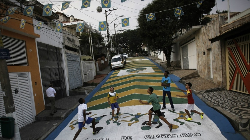 Children play soccer on the street decorated with graffiti in reference to the 2014 World Cup in Sao Paulo.