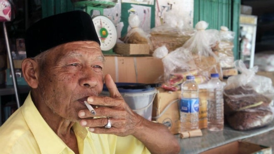 A vendor of locally grown tobacco smokes a cigarette in a market in Indonesia. (REUTERS/Junaidi Hanafiah)