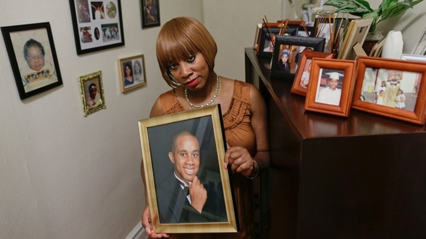 In this June 25, 2014 photo, Tracie Morales stands with a photo of her son, Jamal Polo in New York. Polo committed suicide in May 2012 while jailed on sexual misconduct charges. Investigative documents obtained by The Associated Press on the 11 suicides in New York City jails over the past five years show that in at least nine cases, protocols and safeguards designed to prevent inmates from harming themselves were not followed. (AP Photo/Julie Jacobson)