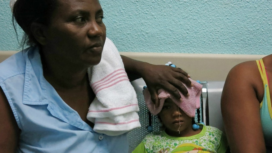 Five-year-old Karla Sepulveda, who suffers chikungunya fever symptoms, waits with her grandmother for treatment in the pediatric area of a public hospital in the coastal town of Boca Chica, Dominican Republic.