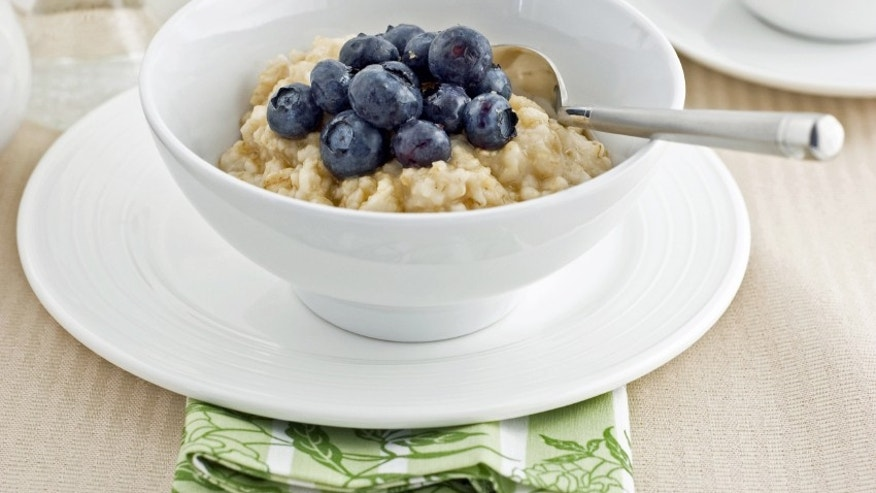 Large flake whole oatmeal with blueberries and brown sugar on white china makes a healthy breakfast