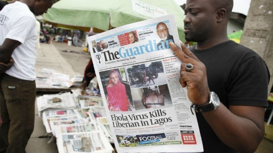 A man reads a local newspaperson a street with the headline Ebola Virus kills Liberian in Lagos, in Lagos Nigeria, Saturday, July 26, 2014. (AP Photo/Sunday Alamba)