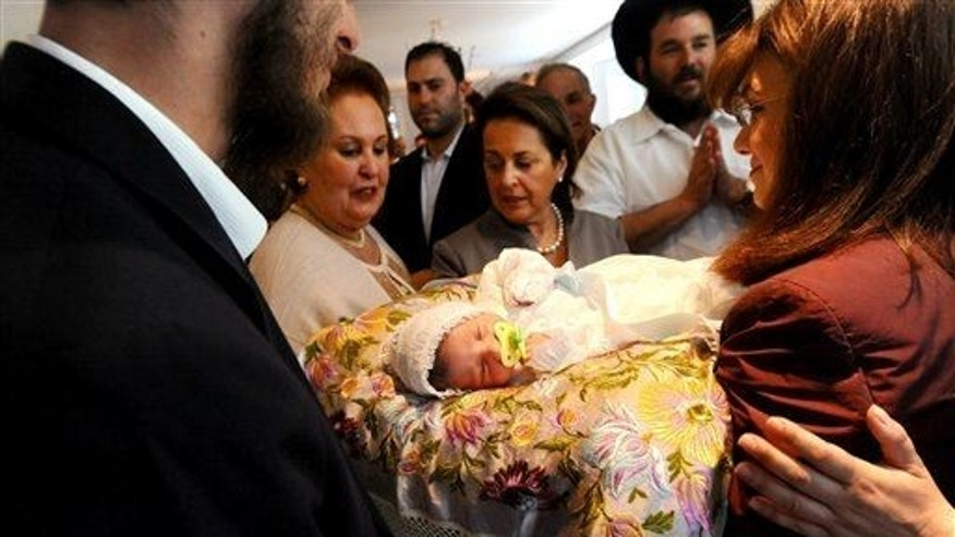 In this Sunday, May 15, 2011 photo, Benjamin Abecassis rests on a pillow sounded by family members, immediately following his Bris, a Jewish circumcision ceremony in San Francisco.