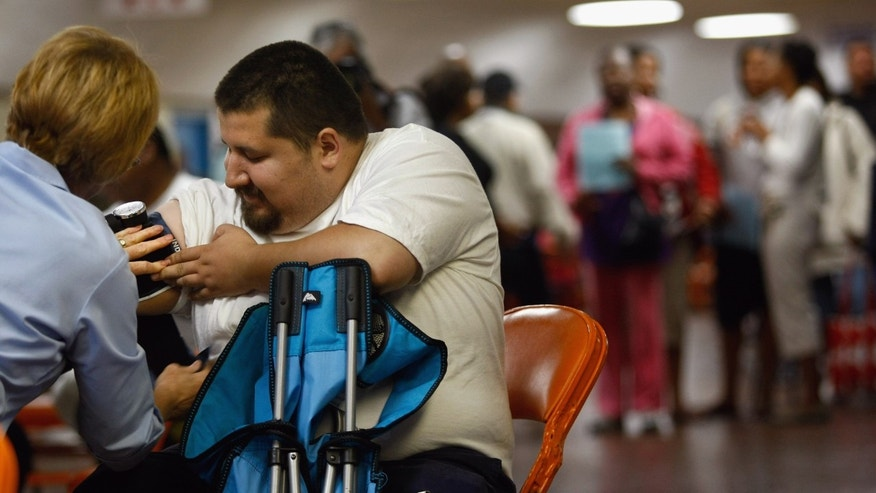 Marza Topete has his blood pressure taken at the Forum arena at a free health clinic on August 11, 2009, in Inglewood, Calif. Hundreds of people, most without health nor dental insurance, waited outside most of the night for the first day of the clinic. (Photo by John Moore/Getty Images)