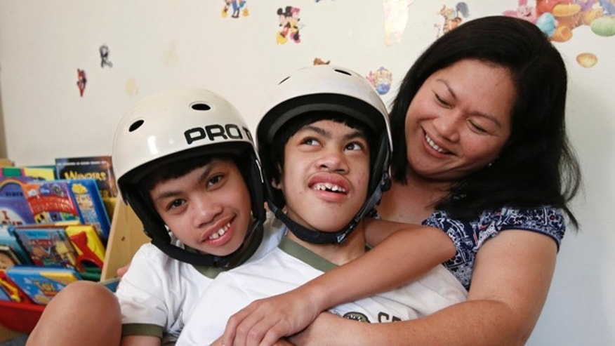 Formerly conjoined twins Clarence, left, and Carl Aguirre, 12, embrace while relaxing with their mother Arlene at the family's home in Scarsdale, N.Y., Thursday, July 31, 2014.  On Monday, Aug. 4, the family will celebrate the 10th anniversary of the surgery that separated the twins at Montefiore Hospital in the Bronx, where the surgery was performed. (AP Photo/Kathy Willens)