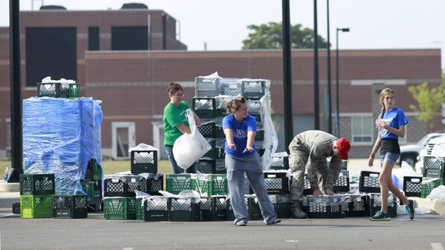 Volunteers coordinate a fresh drinking water distribution point, Sunday, Aug. 3, 2014, at Woodward High School in Toledo, Ohio. More tests are needed to ensure that toxins are out of Toledo's water supply, the mayor said Sunday, instructing the 400,000 people in the region to avoid drinking tap water for a second day. Toledo officials issued the warning early Saturday after tests at one treatment plant showed two sample readings for microsystin above the standard for consumption, possibly because of algae on Lake Erie. (AP Photo/Haraz N. Ghanbari)