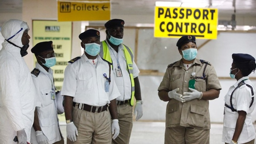 Nigeria health officials wait to screen passengers at the arrival hall of Murtala Muhammed International Airport in Lagos, Nigeria, Monday, Aug. 4, 2014. (AP Photo/Sunday Alamba)