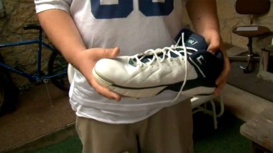 Dakota Deal, 13, who suffers from a rare form of gigantism holds up a pair of shoes he received as a donation after local media covered his story.