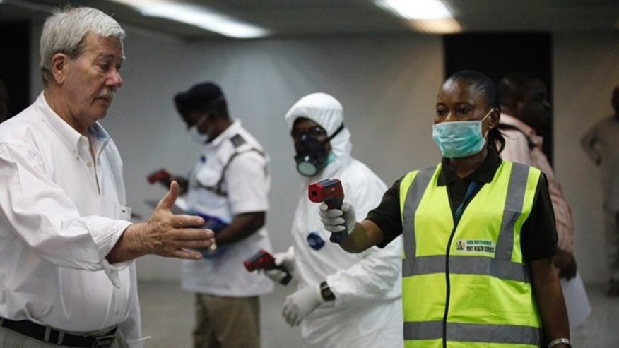 Nigerian port health officials uses a thermometer on a worker at the arrivals hall of Murtala Muhammed International Airport in Lagos, Nigeria,  Wednesday, Aug. 6, 2014. A Nigerian nurse who treated a man with Ebola is now dead and five others are sick with one of the world's most virulent diseases, authorities said Wednesday as the death toll rose to at least 932 people in four West African countries. (AP Photo/Sunday Alamba)