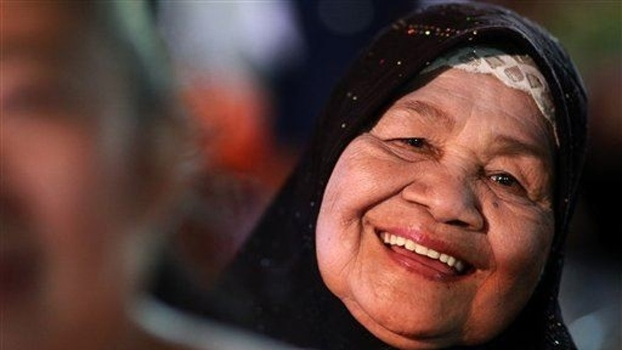 "A woman flashes a smile during an event called ""Return Happiness to Thai People"" in Bangkok in June."