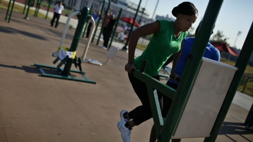 A woman works out in an outdoor exercise area at Macombs Dam Park in the Bronx section of New York City, September 13, 2012. (REUTERS/Mike Segar)