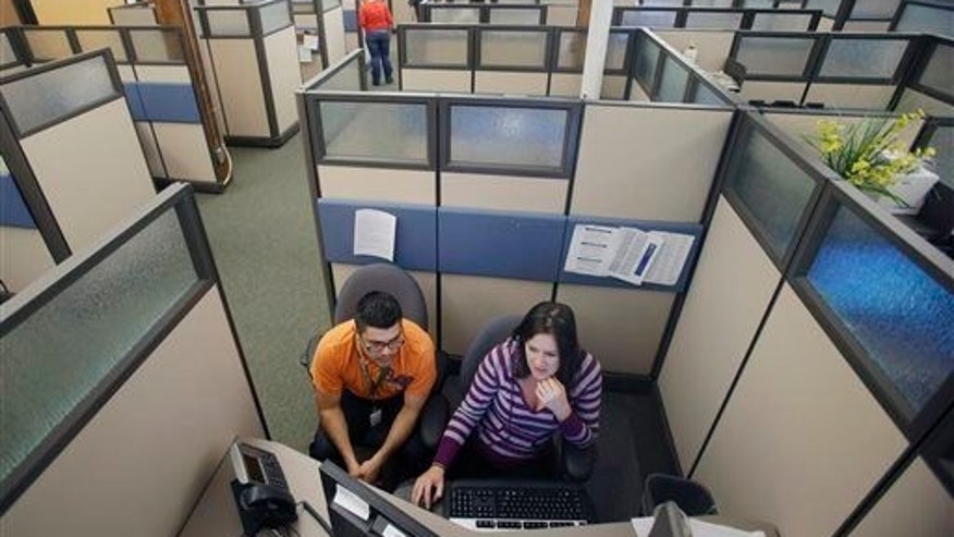 Workers are shown in a cubicle at MNsure contact center in St. Paul, Minn., in 2013.