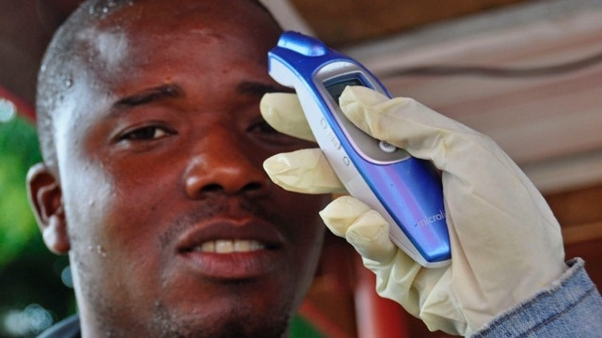 August 9, 2014: A man's temperature is measured before he is allowed into a business center, as fear of the deadly Ebola virus spreads through the city of Monrovia, Liberia. (AP Photo/Abbas Dulleh)
