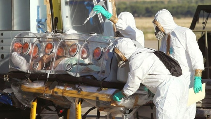 August 7, 2014: In this photo provided by the Spanish Defense Ministry, aid workers and doctors transfer Miguel Pajares, a Spanish priest who was infected with the Ebola virus while working in Liberia, from a plane to an ambulance as he leaves the Torrejon de Ardoz military airbase, near Madrid. (AP Photo/Spanish Defense Ministry)