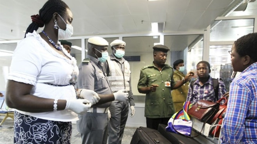 Nigerian custom officers wearing face masks and gloves screen passengers arriving at Nnamdi Azikiwe International Airport in Abuja August 11, 2014. CREDIT: REUTERS/AFOLABI SOTUNDE