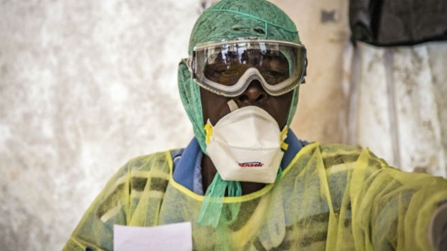 In this photo taken Monday, Aug. 11, 2014, a health worker examines patients for Ebola inside a screening tent, at the Kenema Government Hospital around186 miles from the capital city of Freetown in Kenema, Sierra Leone. (AP Photo/ Michael Duff)
