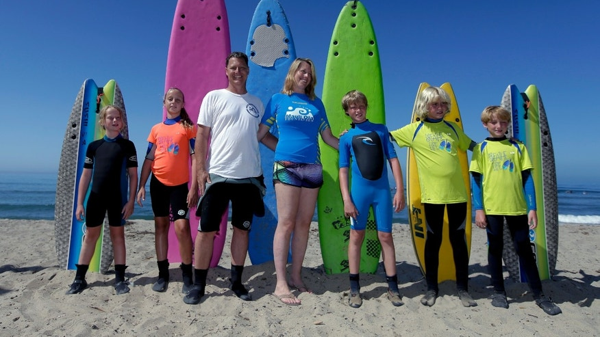 In this July 24, 2014 photo, the Montelone family, from left, Grace, 8, Brooke, 10, Rob, Paulette, Brian, 10, Michael, 12, and Gavin, 8, pose for a family picture on the beach in San Clemente, Calif. Three of the Montelone's five children, who have cystic fibrosis, are part of a growing number of people to take advantage of the health benefits that come with surfing. (AP Photo/Chris Carlson)