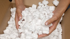 Woman holding heap of packing peanut, close-up of hands
