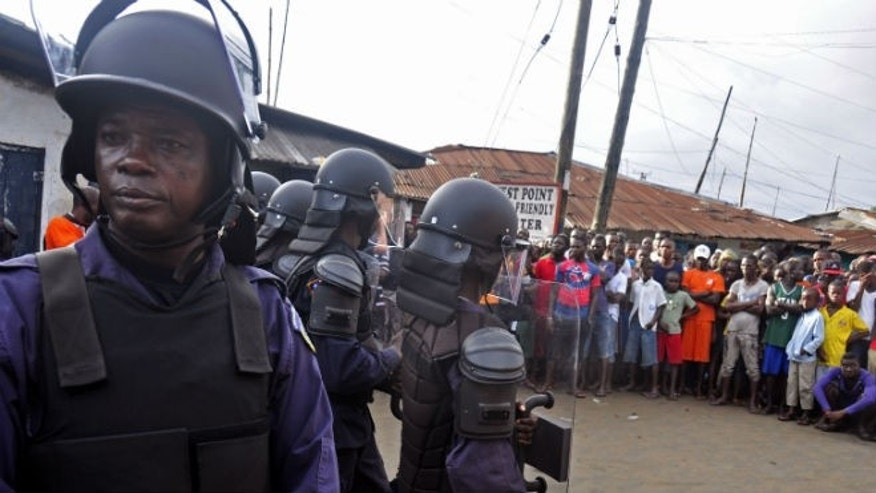 Liberia security forces dressed in riot gear, left, control a crowd of people in the West Point area, as the government clamps down on the movement of people to prevent the spread of the Ebola virus in Monrovia, Liberia, Wednesday, Aug. 20, 2014.  (AP Photo/Abbas Dulleh)