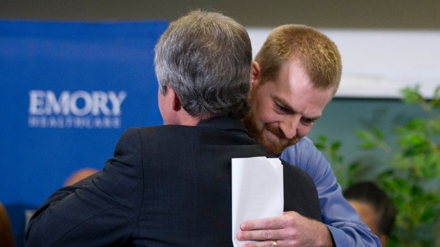 Ebola victim Dr. Kent Brantly, right, hugs a member of the medical staff that treated him, after being released from Emory University Hospital Thursday, Aug. 21, 2014, in Atlanta. (AP Photo/John Bazemore)