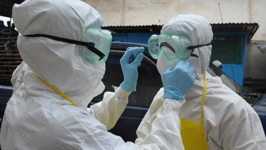 Health workers wearing protective clothing prepare themselves before to carrying an abandoned dead body presenting with Ebola symptoms at Duwala market in Monrovia August 17, 2014. REUTERS/2Tango