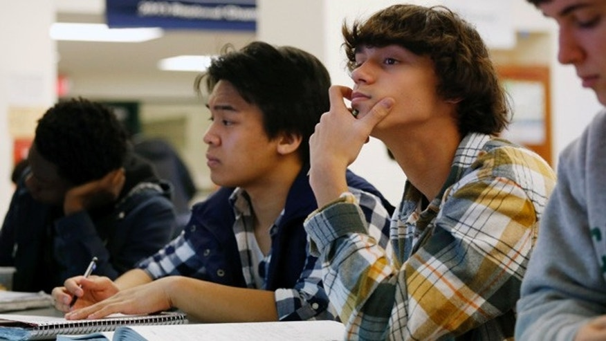 FILE - In this Feb. 7, 2014 file photo, students Julian Lopez, second left, Ben Montalbano, second right and James Agostino, right, listen during their AP Physics class at Woodrow Wilson High School in Washington. A new policy from the American Academy of Pediatrics recommends delaying classes for all teens until at least 8:30 a.m. to curb their widespread lack of sleep, which has been linked with poor health, bad grades, car crashes and other problems. (AP Photo/Charles Dharapak, File)