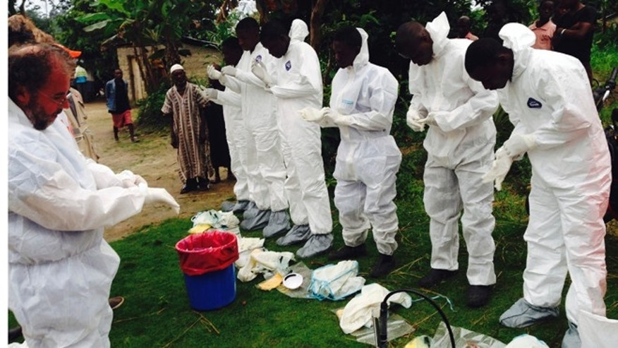 Aug. 2, 2014: Volunteers prepare to remove the bodies of people who were suspected of contracting Ebola and died in the community in the village of Pendebu, north of Kenema.