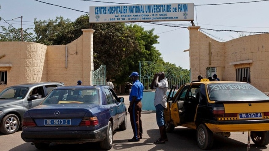August 29, 2014: A security guard, center left,  working at the University Hospital Fann, speaks to people inside a car as a man is treated for symptoms of the Ebola virus inside the Hospital in Dakar, Senegal. (AP Photo/Jane Hahn)